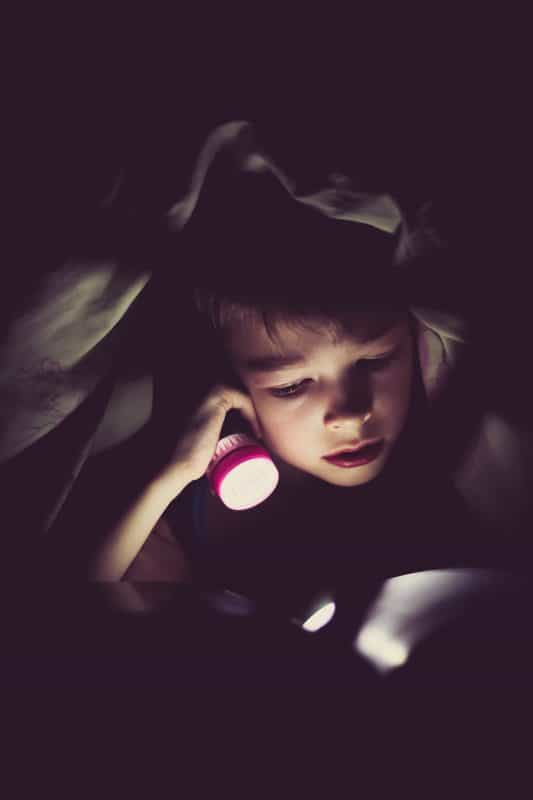Picture Child Reading Under the Blanket with Flashlight