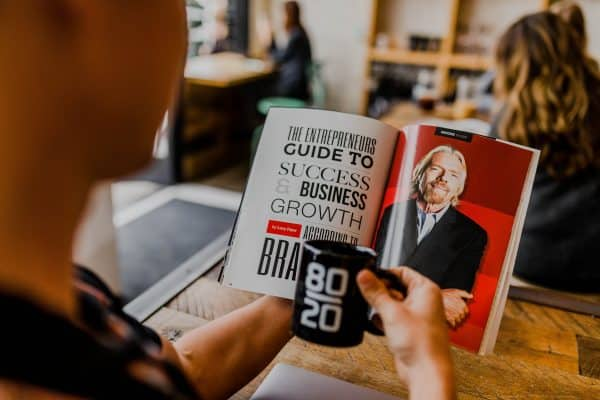 Reading business book with coffee mug