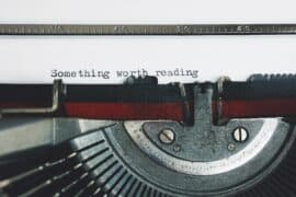 Featured image typewriter typing in a white paper something worth reading